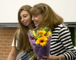 Sandy Spiewak receives flowers from a TPC Teen at end of year event
